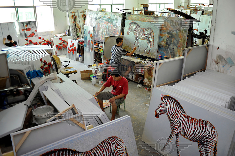 Painters at work in one of the production rooms at Shenzhen Free Cloud Arts and Crafts Co. Dafen is home to an art industry producing replicas, as well as original works, of pieces by the world's great artists for sale overseas. The success of this business has attracted more and more trained artists to the town seeking an opportunity to make a living.
