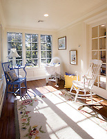 Traditional sun filled nursery with bassinet, rocking chair, french door and wood plank flooring.
