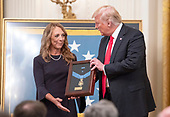 Valerie Nessel, widow of Technical Sergeant John A. Chapman, United States Air Force, left, stands with US President Donald J. Trump, center, as she accepts the Medal of Honor posthumously from the President during a ceremony in the East Room of the White House in Washington, DC on Wednesday, August 22, 2018.  Sergeant Chapman is being honored for his actions on March 4, 2002, on Takur Ghar mountain in Afghanistan where he gave his life to save his teammates.<br /> Credit: Ron Sachs / CNP