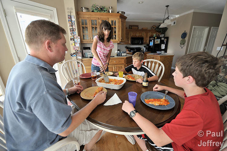 Todd and Brenda Mitton, along with their sons Blake, 10, and Grant 13, share dinner in their Kearney, Missouri, home. Todd's work with the Missouri Air National Guard often requires him to be gone away from home for long periods of time.