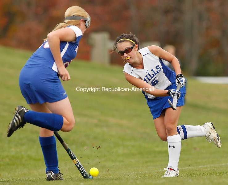 Burlington, CT- 18, October 2010-101810CM03  Nonnewaug's Caitlin Drakeley (left) defends as Lewis Mills' Kristen Van Gilst strikes the ball during Berkshire Field Hockey action Monday afternoon in Burlington.  Nonnewaug blanked Mills 3-0, remaining undefeated on the season.  Christopher Massa Republican-American