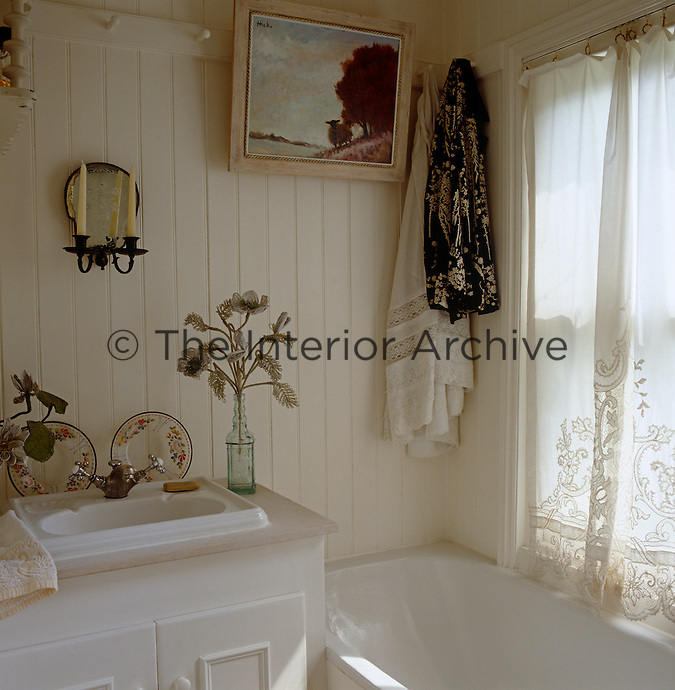 Clothes and a painting hang from a Shaker-style rail of pegs that runs around the walls of the bathroom