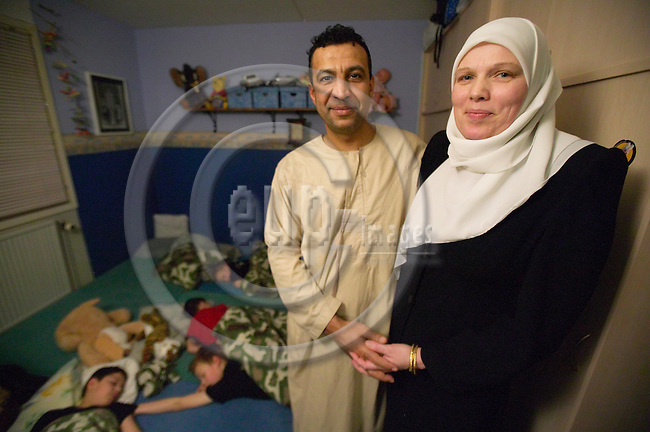 "Muslims in Denmark. Marina Larsen with her palestinian-born husband Khalid Alsubeihi in the bed room of their four boys. Marina wears the hijab to proclaim her strong faith and she is prepared to endure the Islamophbia of many of her fellow Danish nationals as part of the price of having a identity with which she feels comfortable. .Copenhagen, Denmark, 12.01.2005. Photo: Christian T. Joergensen/FotoFactory.dk. ..This image is delivered according to terms set out in ""Terms for Delivery of Photography & Text"". (Please see www.fotofactory.dk for more details)."