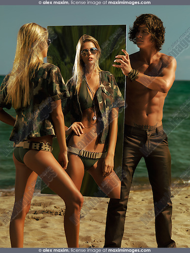 Young man holding a mirror on the beach for a woman in army outfit. High fashion photo.