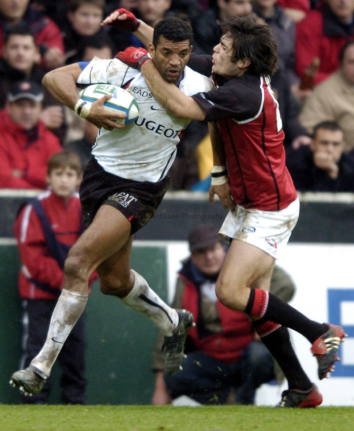Photo: Richard Lane..Edinburgh Rugby v Stade Toulouse. Heineken Cup. 31/01/2003..Emile Ntamack is tackled by Marcus Di Rollo.