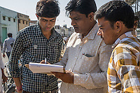 Traders bid for guar harvests from piles that farmers bring in to be auctioned off in Bikaner, Rajasthan, India on October 24th, 2016. Non-profit organisation Technoserve works with farmers in Bikaner, providing technical support and training, causing increased yield from implementation of good agricultural practices as well as a switch to using better grains better suited to the given climate. Photograph by Suzanne Lee for Technoserve