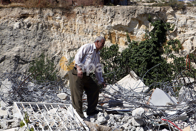 A Member of the Palestinian Ghaith family looks on the rubble of his home after it was demolished by Jerusalem municipality workers in the mostly Arab east Jerusalem neighbourhood of al-Tur on April 29, 2013. Palestinian homes built without an Israeli construction permit are often demolished by order of the Jerusalem municipality. Photo by Sliman Khader