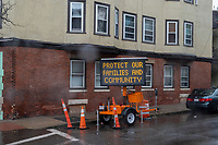 """A temporary sign reads """"Protect Families and Community"""" during the ongoing Coronavirus (COVID-19) global pandemic in Chelsea, Massachusetts, on Mon., April 27, 2020. Chelsea, Mass., is one of the hardest hit communities in Massachusetts with high infection and death rates. As much as 80% of the population works in so-called """"essential jobs,"""" meaning that they continue to work during shelter-in-place orders."""