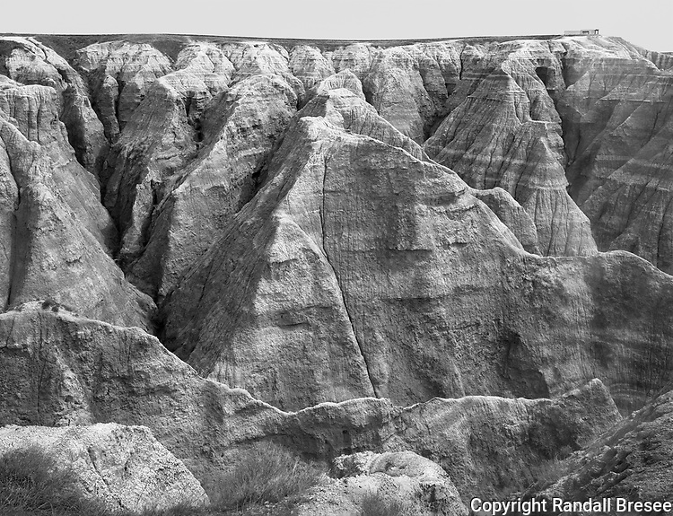 &quot;Big Badlands Overlook from Afar&quot; Badlands National Park, South Dakota<br /> <br /> Scenery in the Badlands National Park includes spectacular layered rock and steep canyons formed by erosion. This black and white photograph shows the Big Badlands Overlook from afar. The overlook point has a bench for sitting enclosed in fencing and can be seen at the upper right of the photo. The bench and fence provide a sense of scale to the huge rock layers and steep canyons in this area.