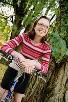 Young woman leaning on bicycle handlebars..MR