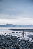 USA, Alaska, Homer, kid play by the edge of Kachemak Bay at Bishop Beach with the Kenai Mountains in the distance