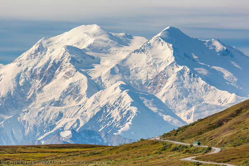 Tour bus travels the Denali park road through thorofare pass, with Denali visible along the Alaska Range horizon.
