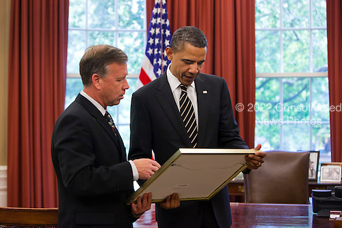United States President Barack Obama accepts a photograph from Space Shuttle Discovery Commander Steve Lindsey while meeting with the Discovery crew in the Oval Office of the White House in Washington, DC, USA, on 09 May, 2011..Credit: Jim LoScalzo / Pool via CNP