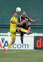 WASHINGTON, DC - AUGUST 4, 2012:  Daniel Woolard (21) of DC United goes up for a high ball with Justin Meram (9) of the Columbus Crew during an MLS match at RFK Stadium in Washington DC on August 4. United won 1-0.