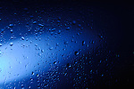 Wet glass with water droplets in blue light abstract artistic background texture