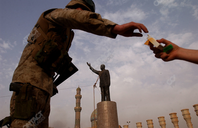 An American soldiers was offered a cigarette by an Iraqi as American forces prepared to pull down a statue of Saddam Hussein in the centre of Baghdad as US forces took control of most of the capital. April 9, 2003