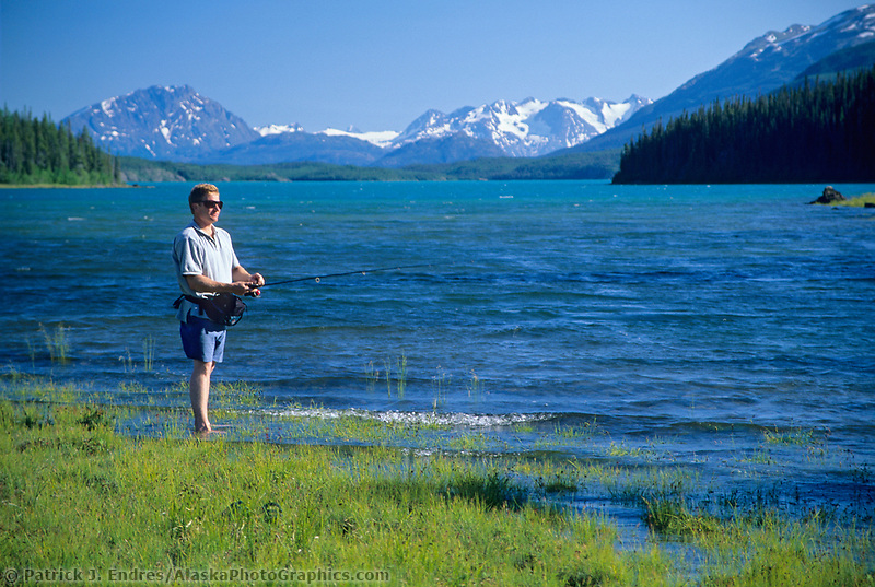 Man fishes along the sunny shore of Atlin Lake, Atlin, BC Canada