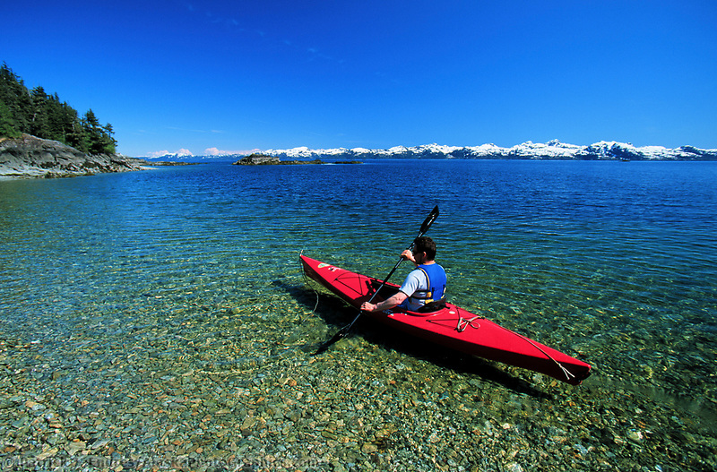 Kayaker paddles in the crystal clear water off Crafton Island, Prince William Sound, Alaska.