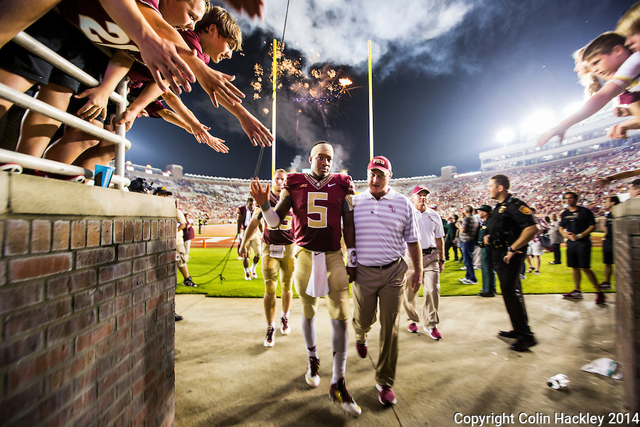 TALLAHASSEE, FL 9/6/14-FSU-CITADEL-Florida State quarterback Jameis Winston walks off the field with Quarterbacks Coach Randy Sanders after The Citadel game Saturday at Doak Campbell Stadium in Tallahassee. The Seminoles defeated the Bulldogs 37-12.<br /> <br /> COLIN HACKLEY PHOTO
