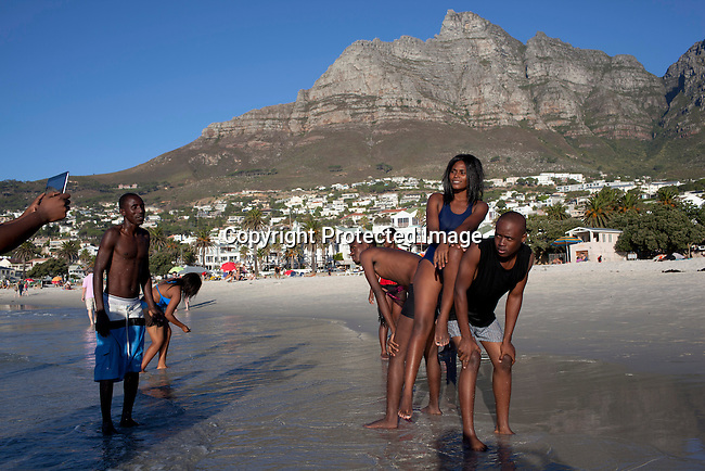 CAMPS BAY, SOUTH AFRICA - MARCH 20: African tourists from Angola at Camps Bay beach on March 20, 2012 in Cape Town, South Africa. The beaches are mostly used by white South Africans or International visitors. (Photo by Per-Anders Pettersson)