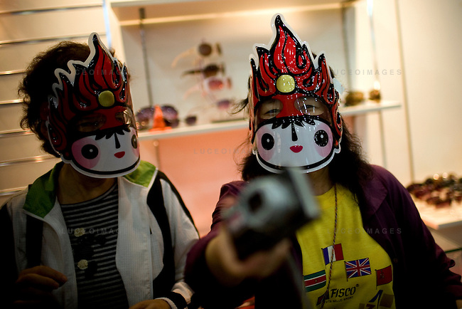 Tourists try on Olympic mascot masks at the Superstore on the Olympic Green in Beijing, China on Thursday, August 21, 2008.  Kevin German