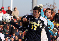 Chris Blais #23 of the University Michigan punches the ball over Hamoody Saad #17 during an NCAA quarter-final match against the University of Maryland at Ludwig Field, University of Maryland, College Park, Maryland on December 4 2010.Michigan won 3-2 AET.