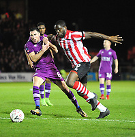 Lincoln City's John Akinde vies for possession with Carlisle United's Mike Jones<br /> <br /> Photographer Andrew Vaughan/CameraSport<br /> <br /> The Emirates FA Cup Second Round - Lincoln City v Carlisle United - Saturday 1st December 2018 - Sincil Bank - Lincoln<br />  <br /> World Copyright © 2018 CameraSport. All rights reserved. 43 Linden Ave. Countesthorpe. Leicester. England. LE8 5PG - Tel: +44 (0) 116 277 4147 - admin@camerasport.com - www.camerasport.com