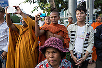 December 15, 2013 - Phnom Penh, Cambodia. Monks document a Cambodia National Rescue Party rally, at the start of weeks of protests calling for a re-election. © Nicolas Axelrod