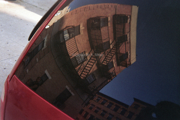 The reflection of an apartment building in the rear window of a van on St. Mark's Avenue.