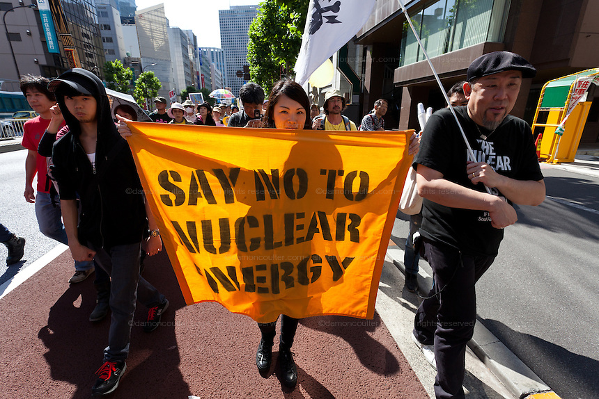 "Anti nuclear protesters carrying  a flag reading, ""say no to nuclear energy"" during a protest march in Tokyo, Japan Sunday June 2nd 2013"