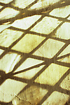 Shadows of diamond-leaded panes of clear or pale yellow glass thrown onto rough white painted wall