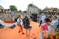 TURNEN: LEMMER: centrum Lemmer, 17-08-2012, Huldiging Olympisch kampioen, turncommentator Hans van Zetten (op de achtergrond), spreekt Epke Zonderland en zijn vriendin Linda Steen (die een rugzak voor hun reis naar Thailand hebben gekregen) toe, moeder Sophie Zonderland, vader Huite Zonderland, Jos Geukers (KNGU-voorzitter), ©foto Martin de Jong