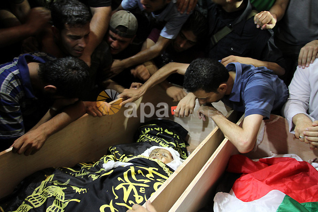 Palestinians mourn over the bodies of Moataz Qreqa, a commander of Islamic Jihad's Al-Quds Brigade, his five-year-old son Islam and his brother Munzer during their funeral in Gaza City on August 20, 2011 after all three were killed when Israeli planes launched air strikes in Gaza in retaliation for suspected Islamist militants killing eight Israelis near the Egyptian border. Photo by Mohammed Asad