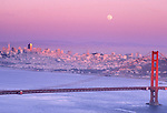 Moonrise over San Francisco; view of San Francisco in the distance and the iconic Golden Gate  Bridge in the foreground. The dusk colors go from pink to blue.
