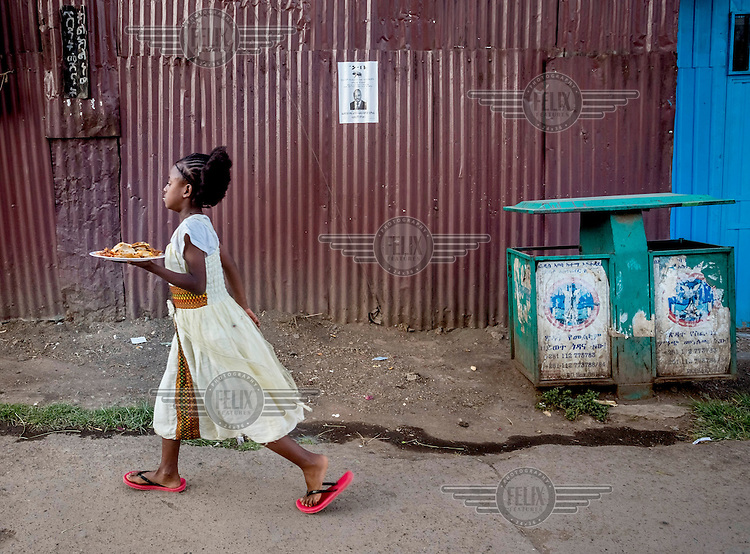A girl carries a plate of food for poor people, wearing traditional Ethiopian clothing, past a small election poster on a red corregated iron fence. The poster is promoting the Ethiopian People's Revolutionary Democratic Front (EPRDF), the country's ruling party since 1991.The symbol of the party is the bee, visible on the poster. <br /> The 2015 National election in Ethiopia will take place on 22 May 2015. Campaigning started in February and will end on 21 May.