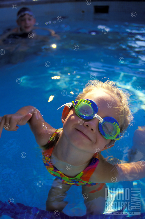 Young girl with goggles in swimming pool