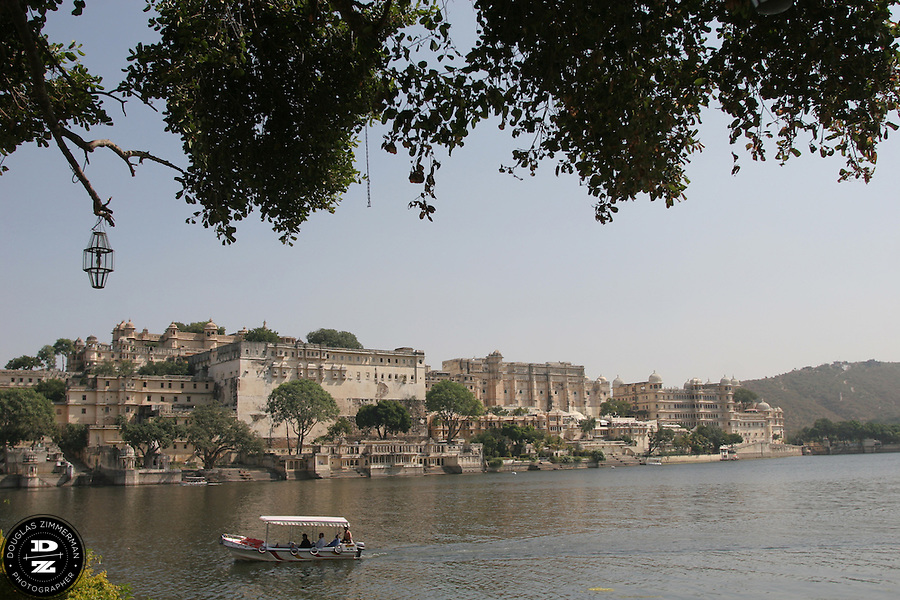 """View of the City Palace of Udaipur, Rajasthan, India across Pichola Lake.  Udaipur sits in a valley surrounded by the Aravalli hills, and at its center is the Pichola Lake.  The scenic city has been described as """"the most romantic spot on the continent of India"""" (by Colonel James Tod).  Photograph by Douglas ZImmerman"""