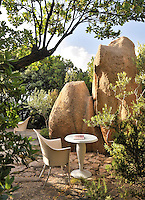 Massive granite boulders litter the landscape around the villa, dwarfing a contemporary table and chair on the patio