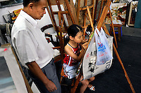 The painter and businessman Huang Jiang in his art school teaching a young girl to draw. In the 1990s Huang Jiang established a studio producing replicas of pieces by the world's great artist for sale overseas. This proved successful and the town attracted more and more trained artists seeking an opportunity to make a living.