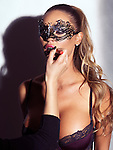 Glamorous sexy woman in mask wearing lingerie having her makeup applied Image © MaximImages, License at https://www.maximimages.com