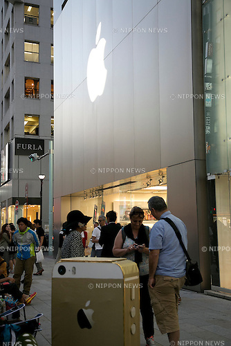 Fans of Apple products wait in front of the Apple Store in Ginza, to buy the new iPhone 5s and lower-cost iPhone 5c, September 17, 2013. During the typhoon Man-yi, the 18th of the season, lashes on Japan this September 16, 2013, Apple fans waited inside the store to protect of the powerful typhoon. According to Apple the mobile phones will be available in Japan, U.S. and other seven countries from September 20. (Photo by Rodrigo Reyes Marin/AFLO)