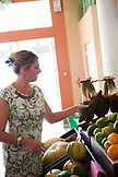 FRENCH POLYNESIA, Raiatea Island. Karine, owner of the Raiatea Lodge shopping for fruits at the Raiatea Market.