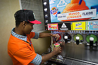 A 7-Eleven employee dispenses Slurpees to hordes of customers in a 7-Eleven store in New York on Thursday, July 11, 2013 (7-11) on Free Slurpee Day. The chain has offered free Slurpees for the past ten years on July, 11. The icy, slushy, syrupy drinks are available in small 7 ounce cups, in regular and diet flavors, and the stores have stocked up with extra barrels of syrup to meet the expected demand. (© Richard B. Levine)