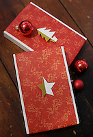 A cut-out star and fir tree made of gold foil are used to decorate two presents wrapped in red and gold paper