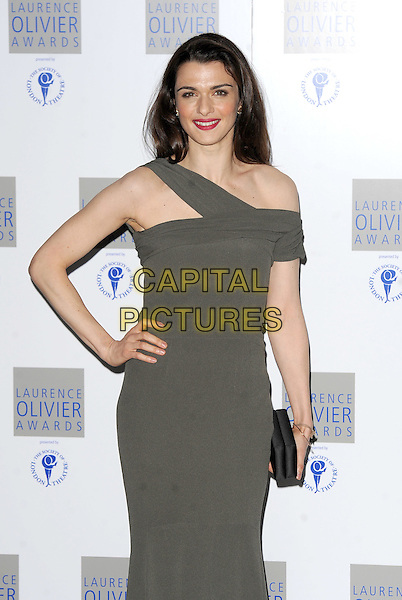 RACHEL WEISZ.The Laurence Olivier Awards 2010, Grosvenor House Hotel, London, England..21st March 2010.half 3/4 length grey gray one shoulder off the dress black clutch bag hand on hip.CAP/BEL.©Tom Belcher/Capital Pictures.