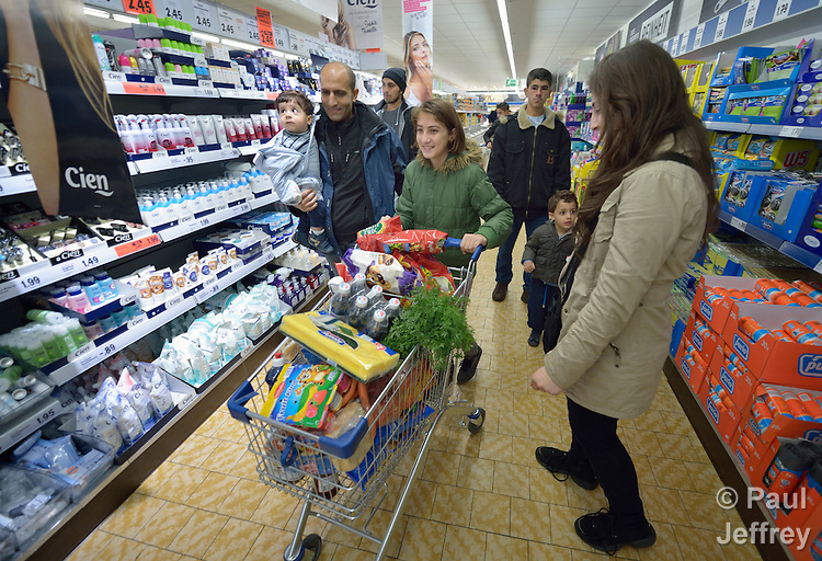 Sherin Ibrahim, 11, pushes a grocery cart in a store in Messstetten, Germany, as two Syrian refugee families shop together. They have all applied for asylum in Germany and are awaiting word on the government's decision. Meanwhile, they share a room in a former army barracks in Messstetten.