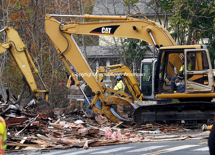 Seymour, CT- 02 November 2014-110214CM02-   Crews demolish the old Seymour Lumber building in Seymour on Sunday. The building, which was declared blighted and containing asbestos, closed down Route 67.  The building located between Route 67 and Little River, required state DOT approval, as well as special fencing to ensure debris didn't fall into the river.   Christopher Massa Republican-American