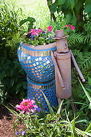 "Rusted iron ""tin man"" ornament next to bright blue mirrored container garden pot of annual flowers geraniums, with ferns and echinacea in shaded spot"