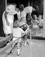 This physical therapist is assisting two polio-stricken children holding on to a rail while they exercise their lower limbs. In the early 1950s there were more than 20,000 cases of polio each year. After the polio vaccination was introduced in 1955 that figure dropped to about 3,000 per year by 1960.