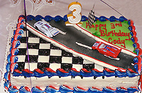 Race car cake waiting to be lit at 3 year old boys birthday party.  Brooklyn Center  Minnesota USA